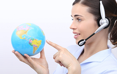 customer service operator woman with headset pointing her finger on globe isolated on white background
